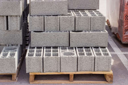 Perforated concrete masonry units on a wooden pallets among other building materials on an outdoor warehouse