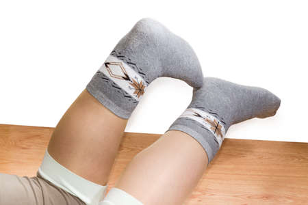 Pair of the wool thermal socks on women legs on the wooden floor on a white background  Stock Photo