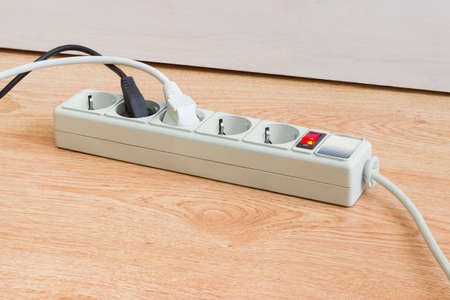 Power strip with electrical sockets of CEE 7 standard, illuminated power circuit breaker and two connected to it power plugs with corresponding mains cables on a wooden surface
