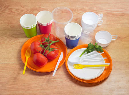 White and orange disposable plastic plates different sizes with tomatoes cluster, disposable plastic forks, spoons and knives on them, plastic and paper disposable cups on a wooden table