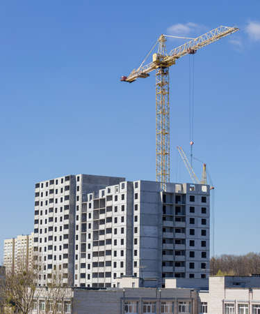 Multi story house from precast concrete panels during construction and building tower crane on background of the sky  Stock Photo