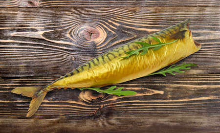 One smoked gutted Atlantic mackerel without head decorated with arugula leaves on an old wooden table