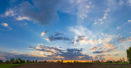 Background of a panoramic view of the sky with cumulus clouds and sunbeams from behind a clouds at sunset in springtime Stock Photo