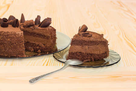 Fragment of the partly cut layered chocolate cake decorated with chocolate chips and sprinkled with cocoa powder on the dark glass dish and slice cake on saucer with spoon on a wooden surface