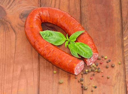 Smoked sausage in natural casing curtailed by a ring with twig of fresh basil and scattered different peppers beside on an old rustic table  Stock Photo