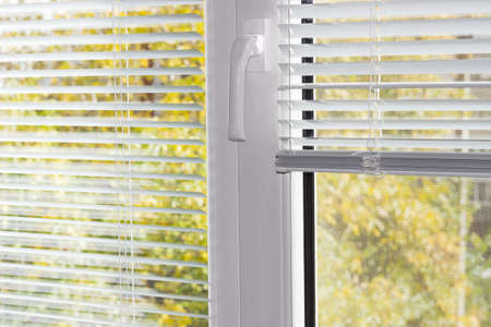 Fragment of the modern plastic window with mosquito net and white Venetian blinds partly raised on one half of the window and blurred view of foliage across slats of blinds
