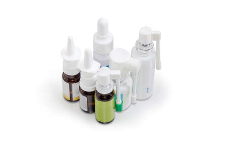 Several different small bottles with medicinal sprays for the treatment of the nose and throat diseases on a white background