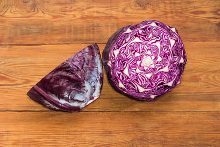 Two halves of head of the red cabbage on an old rustic table  스톡 콘텐츠