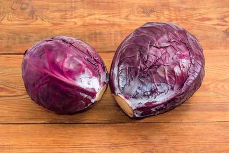 Two whole heads of the fresh red cabbage on an old rustic table