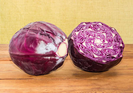 One whole and one half of head of the red cabbage on an old rustic table