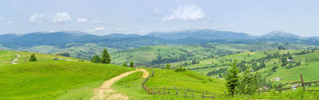 Panorama of the mountain village located in valley and on the mountain slopes on a background of distant ridges in the haze in Carpathian Mountains at summer