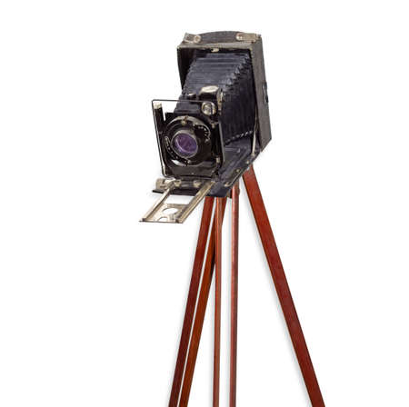 Old used large format folding photographic camera with bellows on a wooden tripod on a white background  Stock Photo