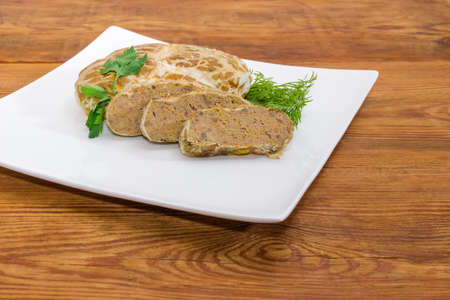 Fragment of the white square dish with partly sliced baked chopped pork liver pate decorated with dill and parsley twigs closeup at selective focus on an old rustic table  Stock Photo