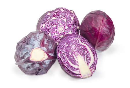 Two halves of the red cabbage head with cut along and cut across and two whole cabbage on a white background