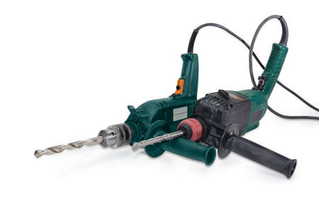 Used working electric conventional drill with metalworking twist drill in chuck and hammer drill with driver bit in chuck on a white background  Stock Photo