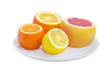 Ripe red grapefruit, orange, lemon and mandarin orange with cut off tops on the white dish on a white background