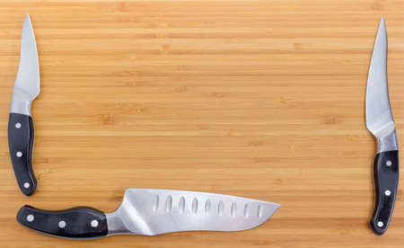 Background of the bamboo cutting board with three different kitchen knives located bottom and sides and empty center