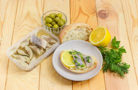 Open sandwich with slices of pickled herring fillet on a saucer, herring in oil marinade in container, white bread, green olives, lemon and greens on a wooden surface