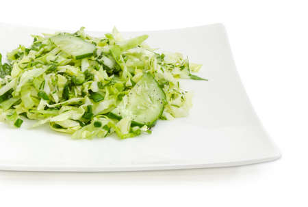 Fragment of square white dish with green vegetable salad made of sliced fresh young cabbage, cucumbers, chopped green onion and greens closeup on a white background