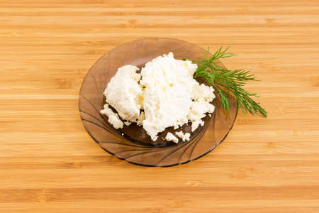 Cottage cheese with twig of dill on the dark glass saucer on a bamboo wooden surface