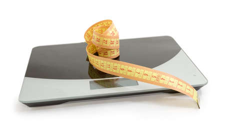 Yellow tape-line on the digital kitchen scale on a white background. Concept of overeating, excess weight and obesity.