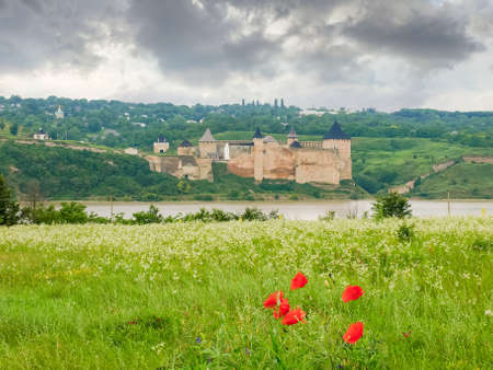 Khotyn fortress built in the 14th century. General view of fortress from the opposite left bank of the Dniester river with grass and flowers on foreground in cloudy weather, Ukraine  Stock fotó