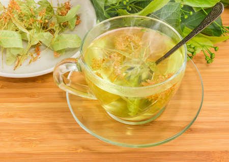 Linden flower tea in the transparent glass cup with tea spoon on a wooden surface on background of dried linden flowers on saucer and fresh linden branches with leaves and buds