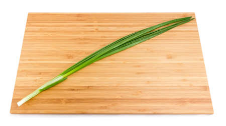 One washed and peeled stalk of green onion on the bamboo cutting board on a white background