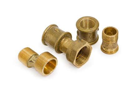 Brass eccentric connector, pipe couplings and other plumbing components on a white background