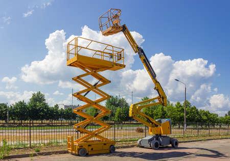 Gelber selbstfahrender Gelenkauslegerlift und Scherenlift auf Hintergrund der Straße mit Bäumen und Himmel
