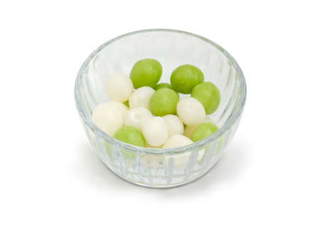 Candies made of the the raisins covered with green and white sugar glaze in the small transparent glass bowl on a white background