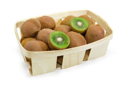 Ripe fuzzy kiwifruits with one fruit cut in half in the wooden basket on a white background Stock Photo