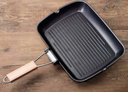Background of the empty grill pan rectangular shape with wooden handle, non-stick coating and a several parallel raised ridges on an old wooden rustic table 免版税图像