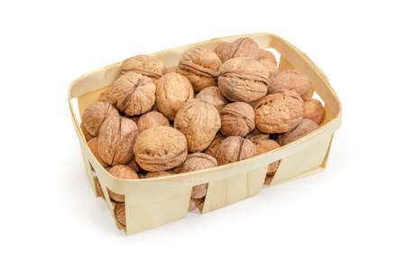 Ripe whole not husked walnuts in the small wooden basket on a white background