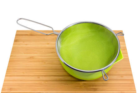 Round stainless steel sieve with wire mesh in green plastic bowl on the bamboo wooden cutting board on a white background Stock Photo