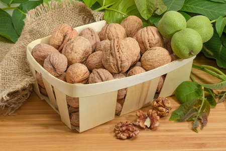Ripe whole not husked walnuts in wooden basket and husked nut kernels beside on a wooden surface on background of walnut branches with unripe fruits 写真素材