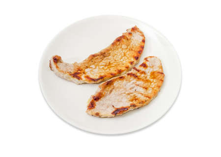 Two grilled sappy boneless pork steaks on the white dish on a white background