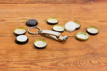 Bottle opener in the form of a keychain with ring among of used different bottle caps on a rustic table at selective focus