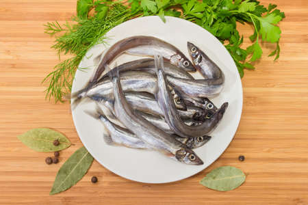 Top view of the white dish with defrosted uncooked capelin, bay leaf, allspice and fresh parsley and dill on a wooden surface Stock Photo