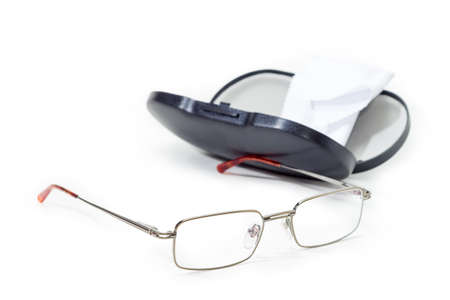 Modern pair of the classic mens eyeglasses in metal frame on blurred background of the open black hard plastic spectacle-case with wipe at selective focus on a white background Stock Photo