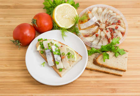 Open sandwich made of brown bread, slices of fillet of pickled Atlantic herring, fresh lemon and choped green onion on a saucer and ingredients for its preparation on a wooden surface