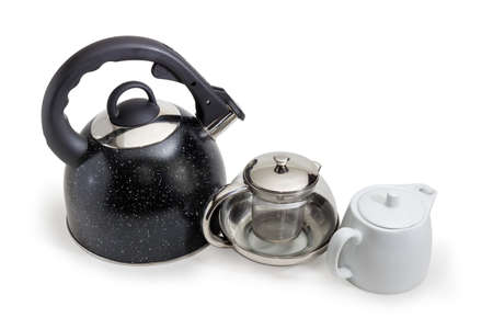 Modern black stainless steel stovetop kettle with steam whistle built-in in spout, glass teapot with strainer and white ceramic teapot on a white background