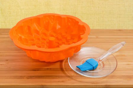 Modern silicone pastry brush on glass saucer and empty silicone cake pan in bundt-style on a wooden bamboo cutting board Фото со стока