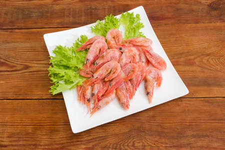 Frozen whole shrimps covered with rime on lettuce leaves on white square dish on a wooden rustic table Stock Photo