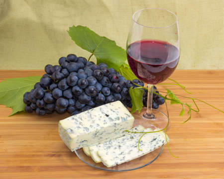 Partly sliced blue cheese on a glass saucer against of glass of red wine and blue grapes on a bamboo wooden cutting board Standard-Bild