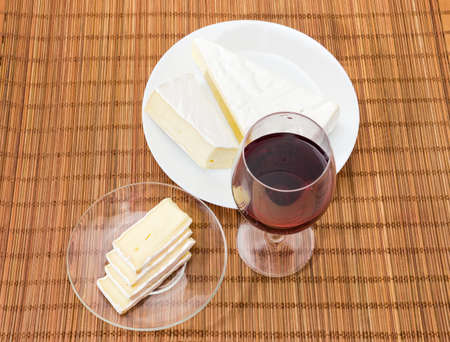 Top view of the glass of red wine, pieces and slices of brie cheese on white dish and glass saucer on the bamboo napkin Archivio Fotografico