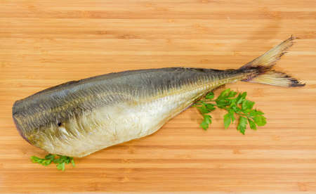 Smoked gutted Atlantic horse mackerel without head with parsley twigs on the wooden bamboo cutting board