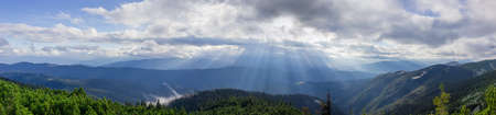 Wide panorama of the ridges, spurs and slopes overgrown with forest and sun beams through the clouds in the Carpathian Mountains