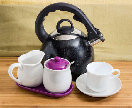 Modern black stainless steel stovetop kettle with steam whistle built-in in spout and empty cup on saucer, sugar bowl, creamer on a bamboo wooden surface