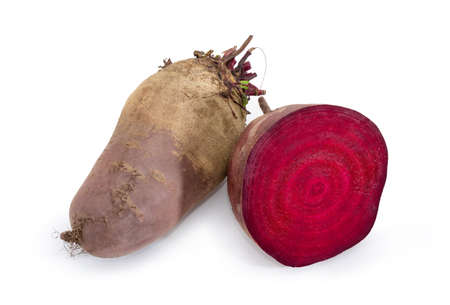 Whole and half of the uncooked red beetroots on a white background Фото со стока